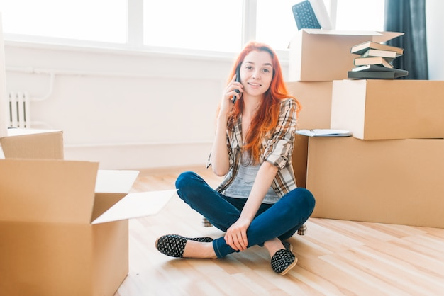 Junge frau, die auf dem boden zwischen pappkartons sitzt und per handy, einweihungsparty spricht. umzug in ein neues zuhause