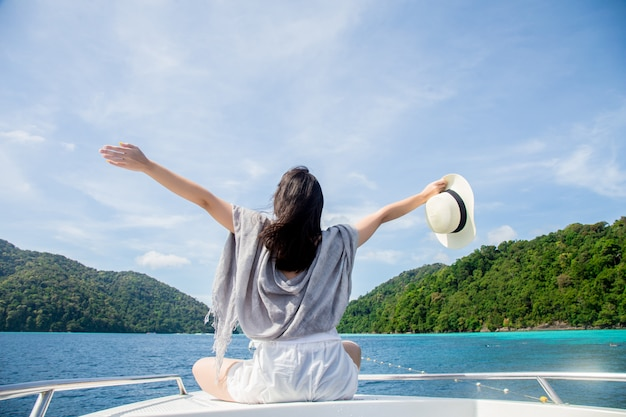 Junge frau, die auf dem boot sich entspannt und vollkommenes meer schaut