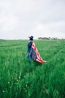 Junge frau, die auf dem gebiet mit amerikanischer flagge bleibt