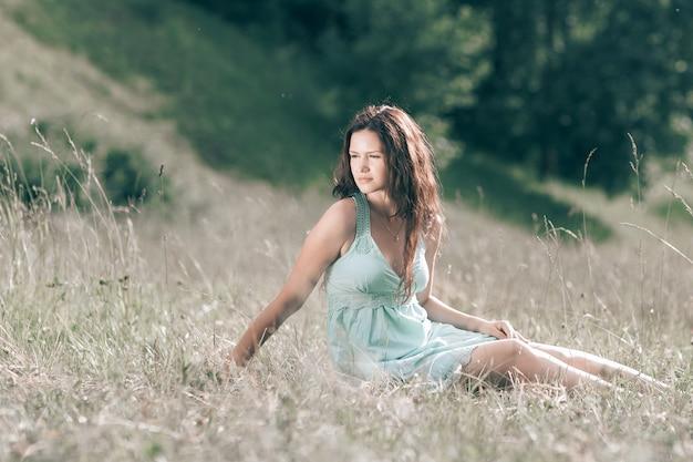 Junge frau, die auf dem gras einer sommerwiese sitzt