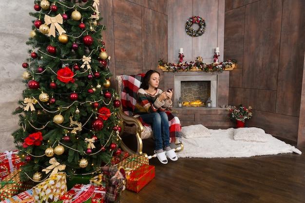 Junge frau, die auf dem schaukelstuhl im zimmer mit geschmücktem kamin und weihnachtsbaum mit geschenken sitzt und das internet auf ihrem handy bedient