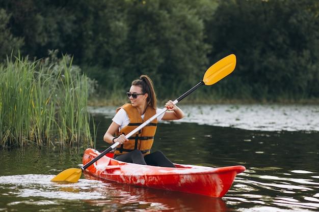 Junge frau, die auf dem see kayak fährt