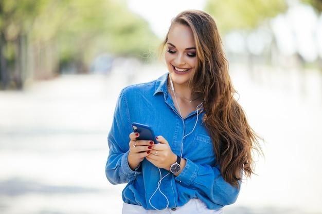 Junge frau, die auf dem smartphone, das in der straße an einem sonnigen tag geht, sms schreibt