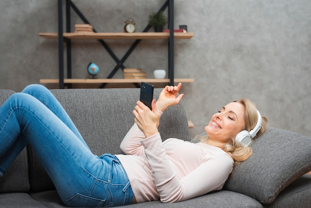 Junge frau, die auf dem sofa genießend liegt, die musik auf kopfhörer von einem intelligenten telefon hörend