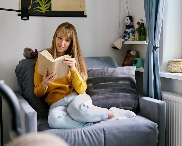 Junge frau, die auf dem sofa sitzt und begeistert das buchkonzept der digitalen entgiftung liest