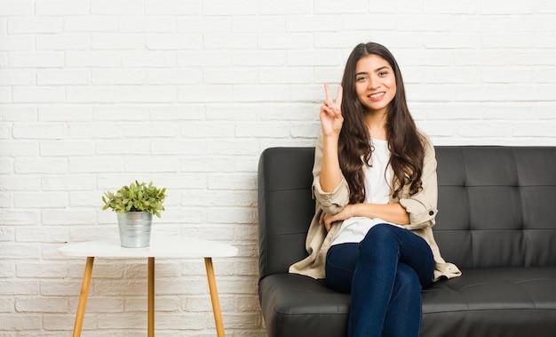 Junge frau, die auf dem sofa sitzt und nummer zwei mit den fingern zeigt
