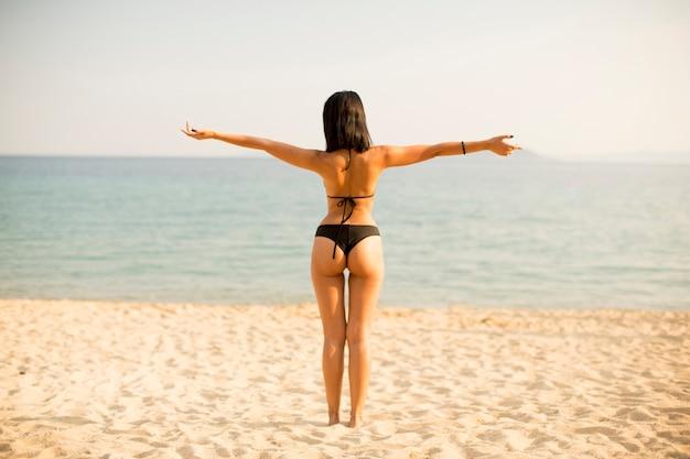 Junge frau, die auf dem strand in einem bikini steht