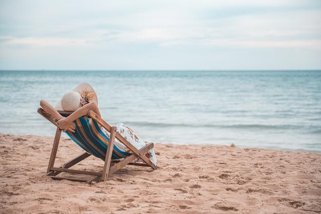Junge frau, die auf dem strandstuhl, sommerferien-feiertagsreise sich entspannt.