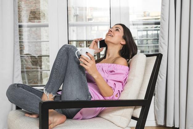 Junge frau, die auf dem stuhl in der hand spricht am handy hält kaffeetasse sitzt