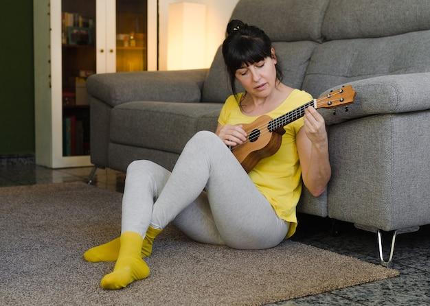 Junge frau, die auf dem teppich in ihrem wohnzimmer sitzt und die ukulele spielt