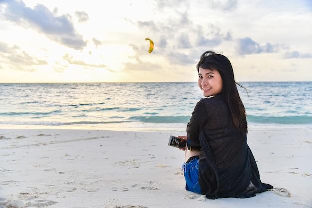 Junge frau, die auf dem tropischen strand, junges woma lächelt und betrachtet die kamera sitzt