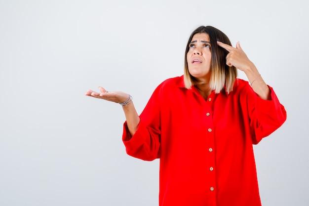 Junge frau, die auf den kopf zeigt, während sie etwas in einem roten übergroßen hemd hält und zögerlich aussieht, vorderansicht.