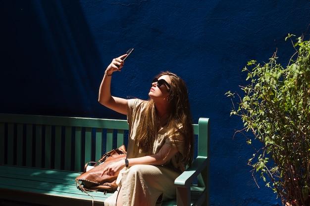 Junge frau, die auf der bank nimmt selfie sitzt