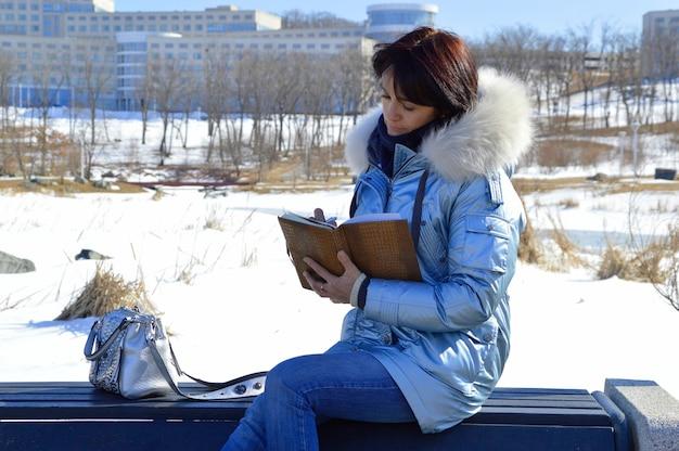 Junge frau, die auf der bank sitzt und in das notizbuch schreibt