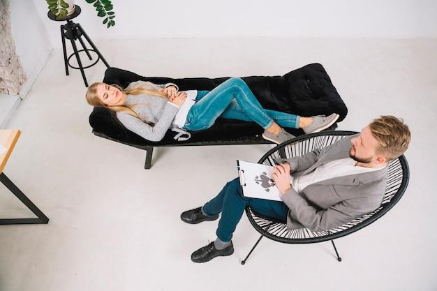 Junge frau, die auf der couch hat eine therapie mit psychologiediagnostik rorschach inkblot test liegt