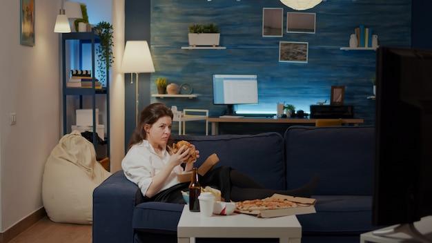 Junge frau, die auf der couch liegt, burger isst und lacht