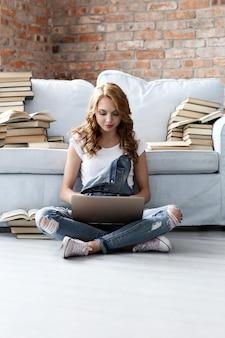 Junge frau, die auf der couch mit laptop und vielen büchern ruht