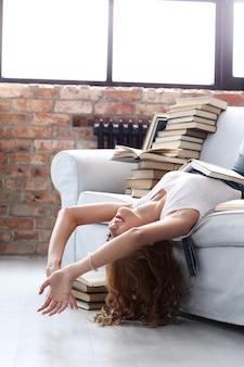 Junge frau, die auf der couch mit vielen büchern ruht