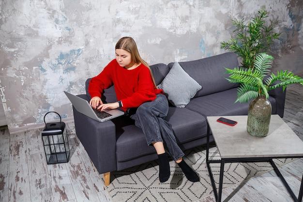 Junge frau, die auf der couch sitzt und den laptopbildschirm betrachtet. eine motivierte, zu hause arbeitende studentin, die online an einem computer arbeitet.