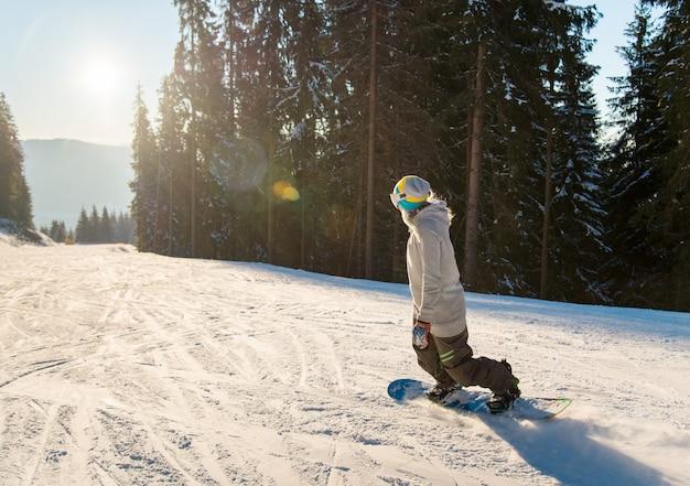 Junge frau, die auf der steigung an einem sonnigen abend des schönen winters snowboarden