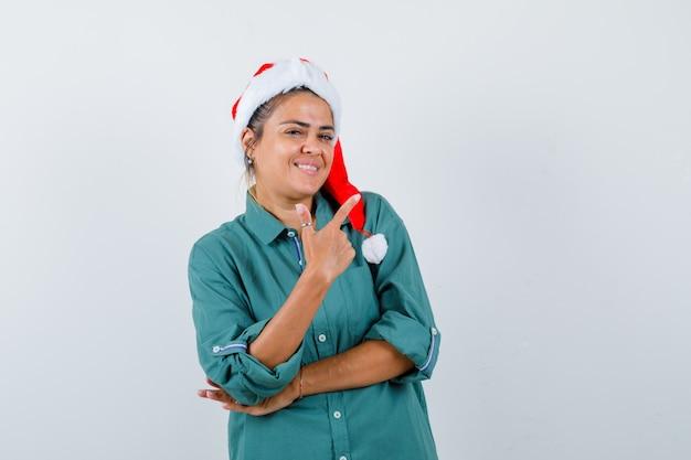 Junge frau, die auf die obere rechte ecke im hemd, in der weihnachtsmütze zeigt und fröhlich schaut. vorderansicht.