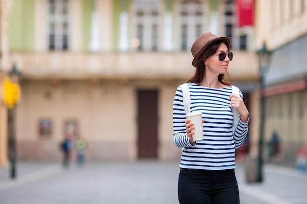 Junge frau, die auf die stadt geht und kaffee in europa trinkt. kaukasische touristen ihren europäischen urlaub in leere stadt genießen