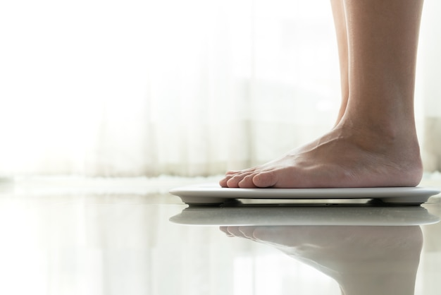 Junge frau, die auf digitaler gewichtsskala steht