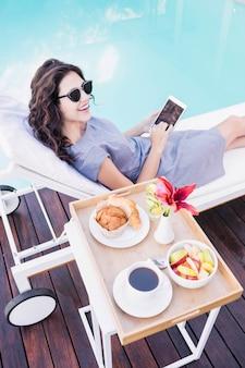 Junge frau, die auf einem sonnenruhesessel sich entspannt und smartphone nahe poolside verwendet