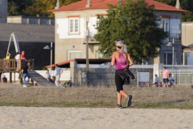 Junge frau, die auf einem stadtstrand, sonnenuntergangsbeleuchtung joggt