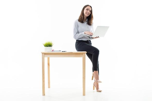 Junge frau, die auf einem tisch sitzt und auf einem computer tippt