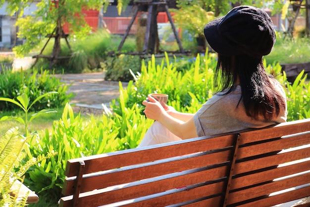 Junge frau, die auf einer bank mit einer tasse kaffee im garten entspannt