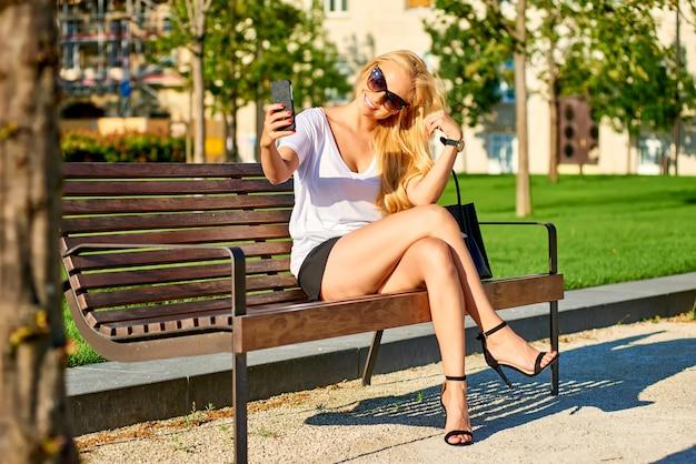 Junge frau, die auf einer bank sitzt und selfies nimmt