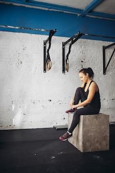 Junge frau, die auf einer box im crossfit-fitnessstudio sitzt und wegschaut