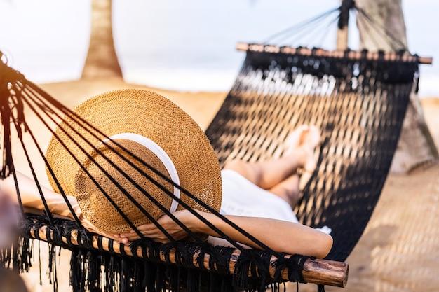 Junge frau, die auf einer hängematte am strand in den sommerferien liegt