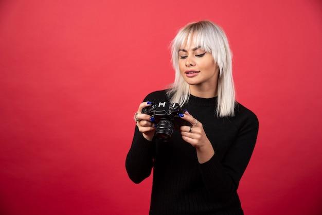 Junge frau, die auf einer kamera auf einem roten hintergrund schaut. hochwertiges foto
