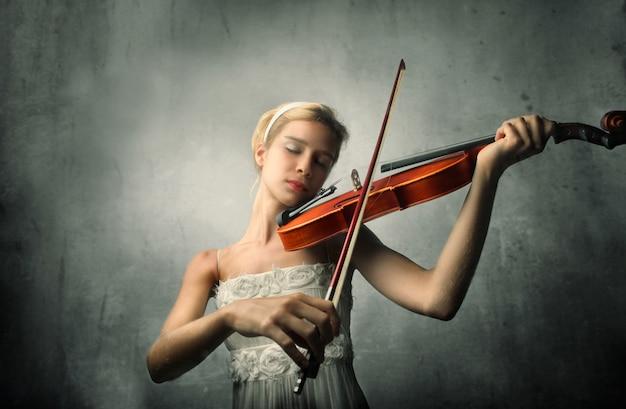Junge frau, die auf einer violine spielt