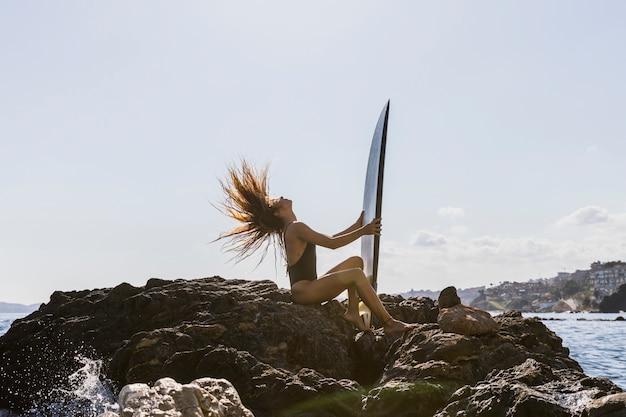 Junge frau, die auf felsigem seeufer mit surfbrett sitzt und haar rüttelt