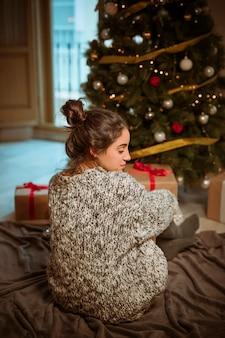 Junge Frau, die auf Fußboden nahe Weihnachtsbaum sitzt