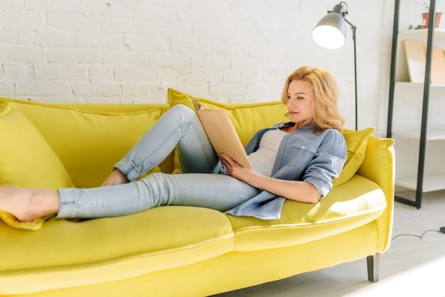Junge frau, die auf gemütlicher gelber couch liegt und ein buch liest