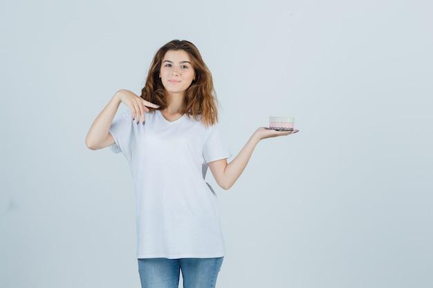 Junge frau, die auf geschenkbox in weißem t-shirt, jeans zeigt und froh schaut. vorderansicht.