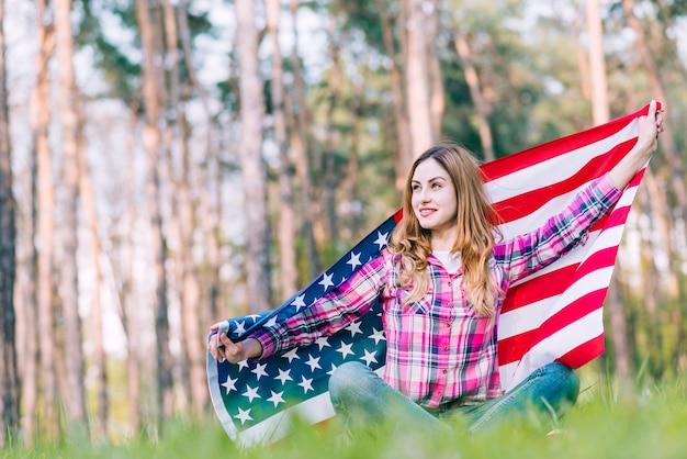 Junge frau, die auf gras sitzt und amerikanische flagge hält