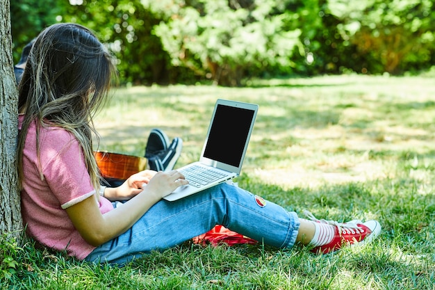 Junge frau, die auf grünem gras sitzt, während laptop verwendet wird