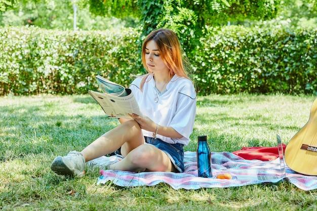 Junge frau, die auf grünem gras sitzt, während tagebuch neben gitarre liest