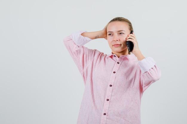 Junge frau, die auf handy in rosa hemd spricht und nachdenklich schaut