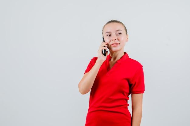 Junge frau, die auf handy in rotem t-shirt spricht und nachdenklich schaut