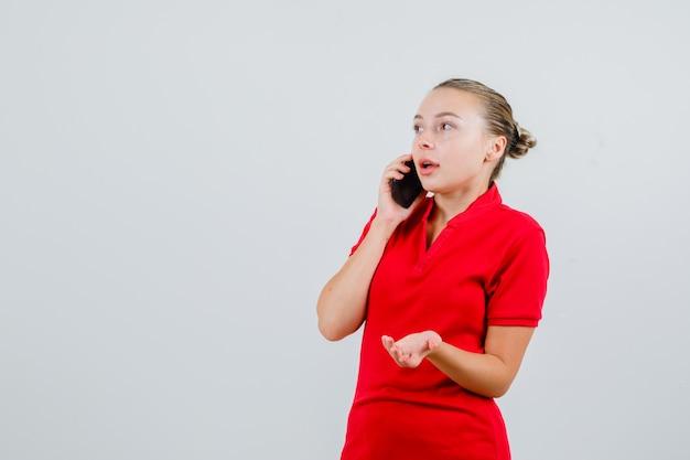 Junge frau, die auf handy in rotem t-shirt spricht und verwirrt schaut