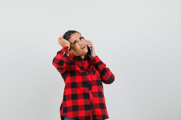 Junge frau, die auf handy spricht, kopf im karierten hemd kratzt und nachdenklich, vorderansicht schaut.