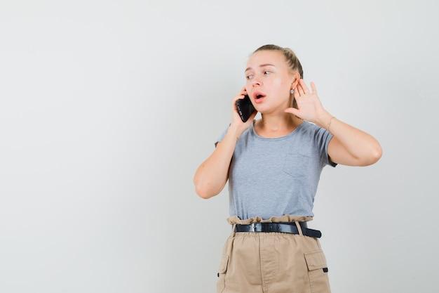 Junge frau, die auf handy spricht und hand hinter ohr in t-shirt, hose, vorderansicht hält.