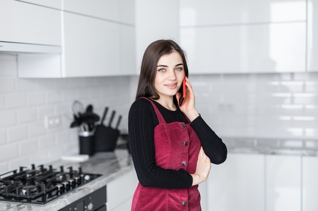 Junge frau, die auf handy spricht, während laptop in der küche zu hause verwendet wird
