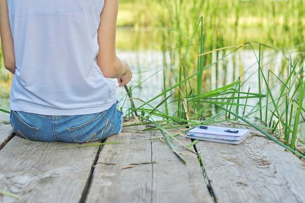 Junge frau, die auf hölzernem pier sitzt und malerische ansicht des seewassers genießt